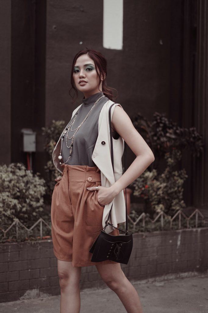 woman posing outside in trendy fashion outfit