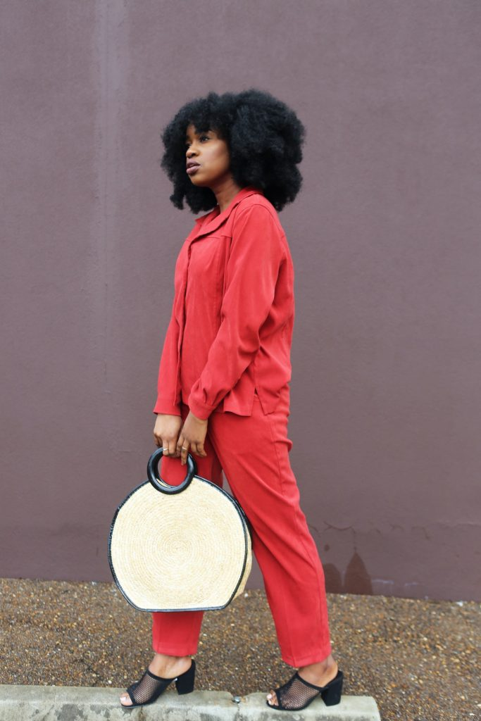 woman posing in red jumpsuit and holding white bag